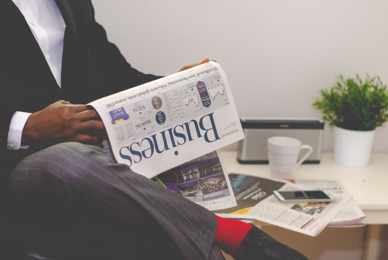 man in suit holding business magazine